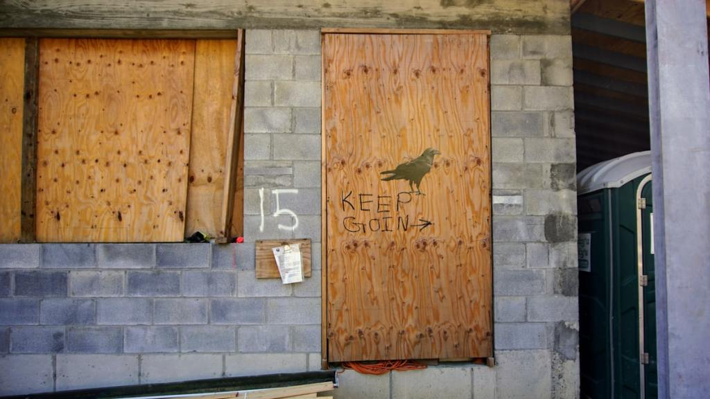 "A brick wall with boarded up windows. On one of the boards, someone has written ""KEEP GOING"" with an arrow and an image of a raven perched above the words."